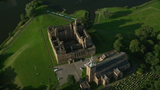 AX111_023 - 6K stock footage aerial video tilt to bird's eye of Linlithgow Palace and St. Michael's Parish Church, Scotland