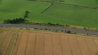 AX111_025 - 6K stock footage aerial video of tracking a black Car on M9 Highway through farmland, Linlithgow, Scotland