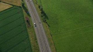 AX111_026 - 6K stock footage aerial video of tracking a black car on M9 Highway through farmland, Linlithgow, Scotland