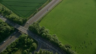 AX111_027 - 6K stock footage aerial video of a black car on M9 Highway through farmland, Linlithgow, Scotland