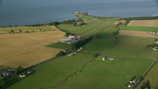 AX111_028 - 6K stock footage aerial video approach Blackness Castle by farm fields and water, Scotland