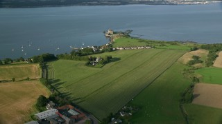 AX111_029 - 6K stock footage aerial video approach Blackness Castle by farmland, Scotland