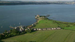 AX111_030 - 6K stock footage aerial video of historic Blackness Castle by farmland and water, Scotland