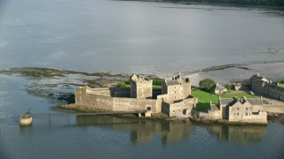 AX111_043 - 6K stock footage aerial video of orbiting around iconic Blackness Castle by River Forth, Scotland