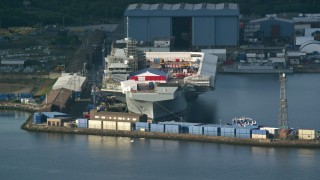 AX111_056 - 6K stock footage aerial video of an aircraft carrier at Rosyth Dockyard on Firth of Forth, Scotland