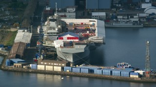 AX111_057 - 6K stock footage aerial video of an aircraft carrier at Rosyth Dockyard on Firth of Forth, Scotland