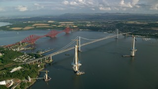 AX111_063 - 6K stock footage aerial video of flying by Forth Road Bridge and Forth Bridge on Firth of Forth, Scotland