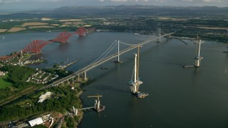 AX111_064 - 6K aerial stock footage video of the Forth Road Bridge and Forth Bridge on Firth of Forth, Scotland