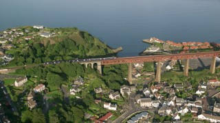 AX111_072 - Aerial stock footage of 6K aerial  video of a commuter train on Forth Bridge, North Queensferry, Scotland