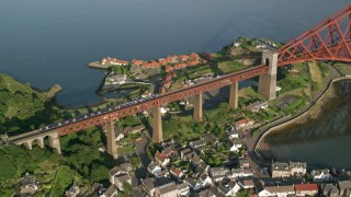 AX111_073 - 6K stock footage aerial video of a commuter train on Forth Bridge in North Queensferry, Scotland