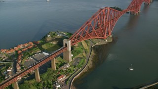 AX111_074 - 6K stock footage aerial video of a commuter train on Forth Bridge over Firth of Forth, Scotland