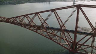 AX111_078 - 6K stock footage aerial video of tracking a commuter train on Forth Bridge over Firth of Forth, Scotland