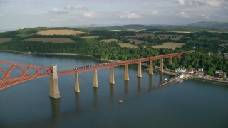 AX111_081 - 6K stock footage aerial video of a view of a commuter train on Forth Bridge over Firth of Forth in Scotland
