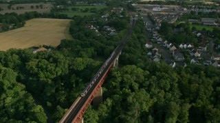 AX111_083 - 6K stock footage aerial video of flying over a commuter train moving between trees on Forth Bridge, Scotland