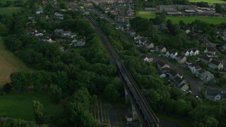 AX111_084 - 6K stock footage aerial video of a commuter train passing through a residential area, Edinburgh, Scotland