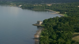 AX111_086 - 6K stock footage aerial video of iconic Barnbougle Castle beside Firth of Forth in Edinburgh, Scotland