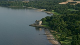 AX111_087 - 6K stock footage aerial video of iconic Barnbougle Castle by Firth of Forth, Edinburgh, Scotland
