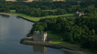 AX111_088 - 6K stock footage aerial video of historic Barnbougle Castle and Dalmeny House by Firth of Forth, Edinburgh, Scotland