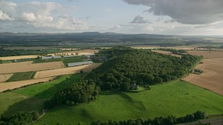 AX111_092 - 6K stock footage aerial video fly past farm, fields, and trees, South Queensferry, Scotland