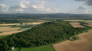 AX111_093 - 6K stock footage aerial video of farm fields and trees, South Queensferry, Scotland