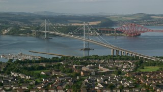 AX111_100 - 6K stock footage aerial video of Forth Road Bridge by residential neighborhood, Edinburgh, Scotland