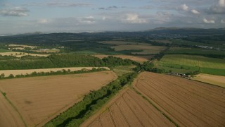 AX111_103 - 6K stock footage aerial video fly over rural landscape of farm fields and trees, Edinburgh, Scotland