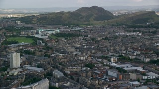 AX111_124 - 6K stock footage aerial video approach Easter Road soccer stadium and Arthur's Seat peak, Edinburgh, Scotland