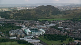AX111_126 - 6K stock footage aerial video of Easter Road soccer stadium and Arthur's Seat mountain, Edinburgh, Scotland