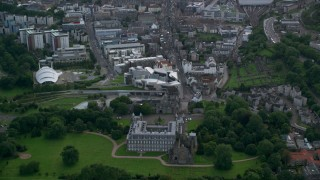 AX111_129 - 6K stock footage aerial video fly over historic Holyrood Palace toward Scottish Parliament, Edinburgh Scotland