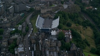AX111_134 - 6K stock footage aerial video fly over Canongate buildings revealing Edinburgh Castle, Scotland