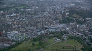AX111_148 - 6K stock footage aerial video of Calton Hill monuments and observatory, and Edinburgh cityscape in Scotland