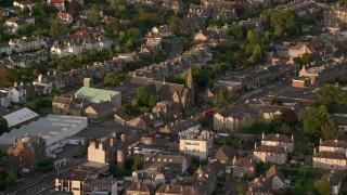 AX112_003 - 6K stock footage aerial video of Saint Ninian's Church and residential neighborhood, Edinburgh, Scotland at sunset