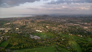 AX112_006 - 6K stock footage aerial video approach neighborhoods, Edinburgh, Scotland at sunset