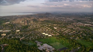 AX112_007 - 6K stock footage aerial video approach residential neighborhoods, Edinburgh, Scotland at sunset