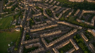 AX112_010 - 6K stock footage aerial video of flying over row houses, Edinburgh, Scotland at sunset
