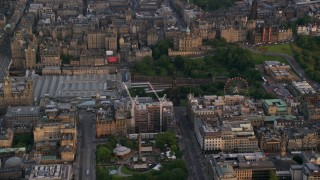 AX112_013 - 6K stock footage aerial video of Scott Monument, St Andrew Square, and train station, Edinburgh, Scotland at sunset