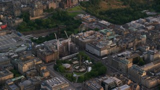 AX112_014 - 6K stock footage aerial video of construction cranes by St Andrew Square, Edinburgh, Scotland at sunset