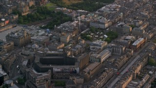AX112_015 - 6K stock footage aerial video of St Andrew Square and shopping mall, Edinburgh, Scotland at sunset