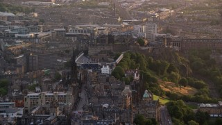 AX112_019 - 6K stock footage aerial video of passing by The Hub and Edinburgh Castle, Scotland at sunset