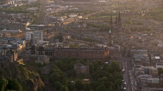 AX112_021 - 6K stock footage aerial video of flying by cityscape and The Hub, Edinburgh, Scotland at sunset