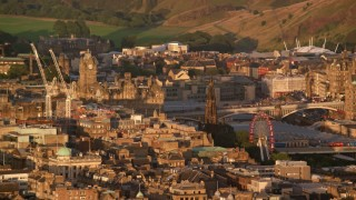 AX112_032 - 6K aerial stock footage video of Balmoral Hotel and Scott Monument in Edinburgh, Scotland at sunset