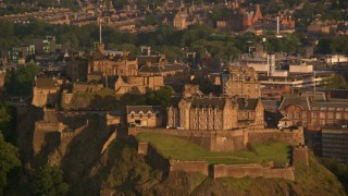 AX112_035 - 6K stock footage aerial video of flying by the hilltop Edinburgh Castle, Scotland at sunset