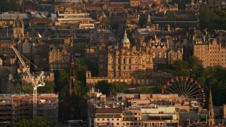 AX112_038 - 6K stock footage aerial video of Lloyds Bank Headquarters office building and ferris wheel, Scotland at sunset