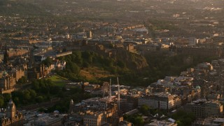 AX112_043 - 6K stock footage aerial video of Edinburgh Castle on a hilltop in Scotland at sunset