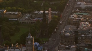 AX112_044 - 6K stock footage aerial video of Scott Monument and ferris wheel, Edinburgh, Scotland at sunset