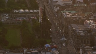AX112_045 - 6K stock footage aerial video of a view of Scott Monument and ferris wheel, Edinburgh, Scotland at sunset