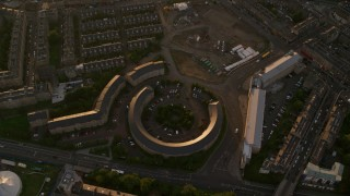 AX112_052 - 6K stock footage aerial video of tilting to a bird's eye view of office buildings at sunset in Edinburgh, Scotland