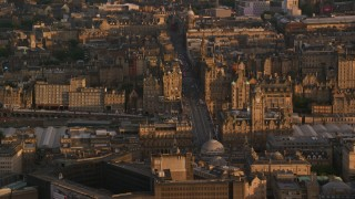 AX112_058 - 6K stock footage aerial video of flying by Balmoral Hotel and North Bridge, Edinburgh, Scotland at sunset