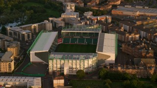 AX112_060 - 6K stock footage aerial video of orbiting Easter Road soccer stadium, Edinburgh, Scotland at sunset