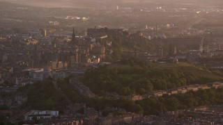 AX112_063 - 6K stock footage aerial video of a view of Edinburgh Castle and Calton Hill, Scotland at sunset